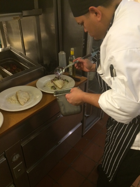 Chef Romero plating multiple dishes during 'The Rush'