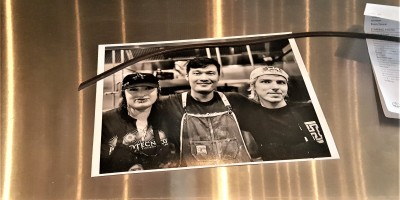 A black and white photograph of Vencio and his co-workers hangs from Aubergine Bistro.